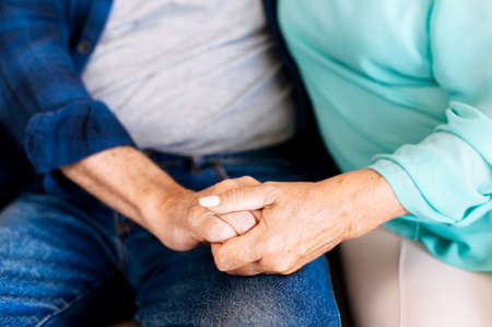 Photo for Senior couple holding hands sitting together at home, faces is not visible. Concept of support and caring in marriage - Royalty Free Image