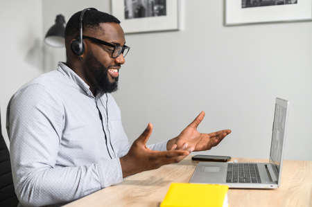 Photo pour Young intelligent African-American teacher sitting at the desk and having coaching session online with students from business school, working on a laptop, using headphones with a microphone - image libre de droit