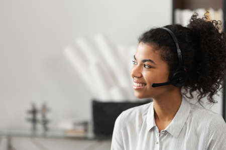 Photo for Young thoughtful African American female sudent in a headset is listening to an online webinar, studing remotely from home or working in the customer service department as a call center operator - Royalty Free Image