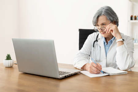 Senior old female doctor with a stethoscope in a lab coat and glasses sitting at the desk and looking at the laptop, studying online, freshening-up her memory, and making notes in the notebook