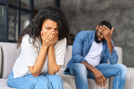 Photo for Young biracial couple relation problem concept, african woman feeling sad and crying after have an argument at home, sad or depressed woman sitting on sofa with her couple, man in defocus sits near - Royalty Free Image