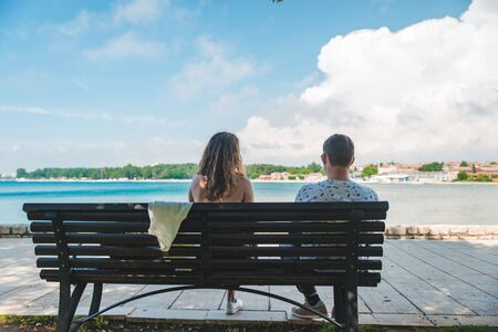 Photo pour couple travelers sitting on bench with sea view resting in shadow. hot summer day - image libre de droit