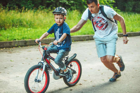 Photo for Lviv, Ukraine - June 23, 2019: father teaching son how to ride bicycle. summer time. public park - Royalty Free Image