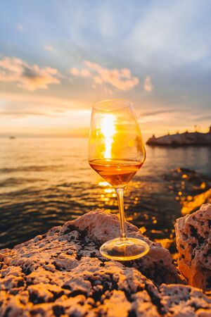 Photo pour glass of wine at rocky sea beach on sunset. copy space. summer vacation - image libre de droit