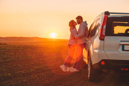 Photo for romantic moment couple kissing on sunset near white suv car copy space. - Royalty Free Image