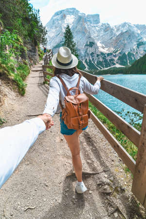 Photo for follow me concept woman walking by trail around lake in mountains. copy space - Royalty Free Image
