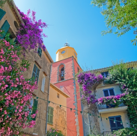 The image of the clock tower with facades of adjacent buildings in beautiful flowers against the blue sky, San Tropez.