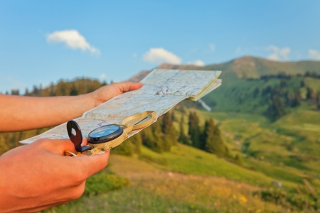 Picture of the tourist's hand with the map using a compass. In the background a beautiful valley with the tops of the mountains at sunset. Switzerland.