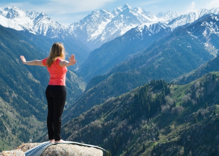The young woman is doing yoga warm-up before the yoga asanas on the summit. On the background is a range of high tops of mountains.