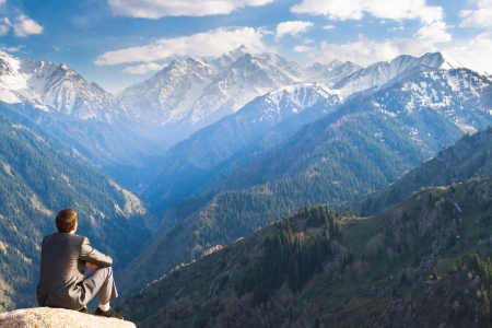 Image of a young businessman who sits on the top of the mountain and looks into the distance to the beautiful mountains, thinking about future plans.