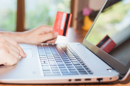 Concept of online payment by plastic card through the Internet Banking. Close-up of human hand for laptop and holding credit card, man is shopping indoor at home