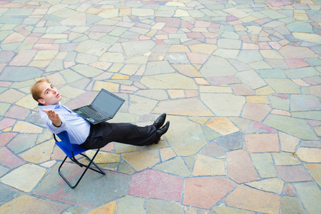Image of the businessman with the laptop looking at the camera and symbolically sending a kiss. Focus is made on top of the background color tile in the street.