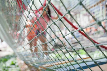 abstract background of rope net with children standing in the children's rope park. Focus on foreground.