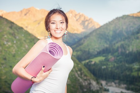 Happy asian woman with yoga mat going to play in sports or fitness exercises outdoor at mountain. Healthy lifestyles concept of body and soul