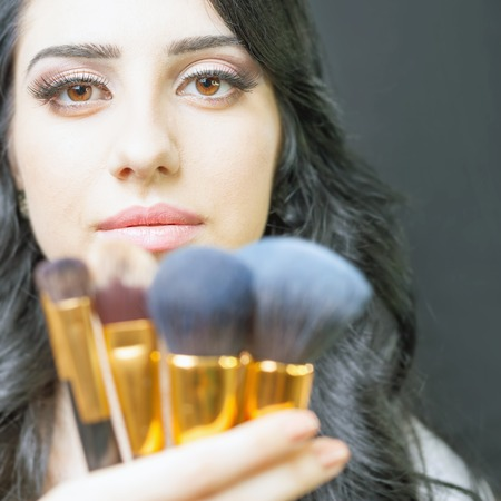 Closeup beautiful arabian woman at beauty salon with a nice makeup. Holding in hands a set of professional makeup brushes on a dark or black background.