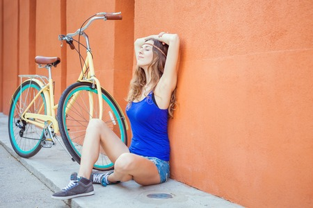 Sexy beautiful caucasian woman sitting near the red wall background, there is a vintage city bicycle and copy space
