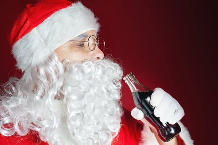 Santa Claus drinking Cola fresh beverage at glass bottle. Christmas holiday, New Year. Copy space for disign, text at red backgroundの写真素材