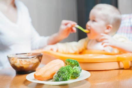 Mom feeds the baby soup. Healthy and natural baby food. Vegetables, carrots, cabbage, broccoli. Child sitting on the highchair at the table.