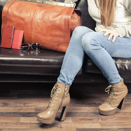 Closeup girl waiting airplane flight in VIP lounge room, airport. Terminal. Leather hand luggage. Business class. VIP lounge. Fashion girl