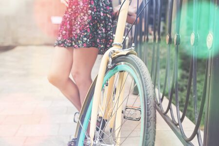 closeup of woman standing near blue vintage city bicycle at the city center at sumer. It is like concept for activity and healthy lifestyle and environmentally friendly transport
