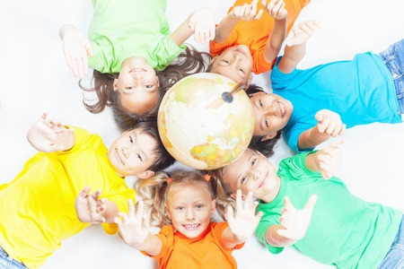 Group of international funny kids. Lying with globe earth, looking up at camera. Smiling. School children learn geography. Multi Ethnic people. World. Ecology. Pure earth. International Children\'s Day