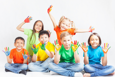 Happy kids with painted hands smiling and posing at white background. Funny children. International Children\'s Day. Indian, asian, caucasian - multiracial ethnicity