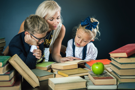 Mother or teacher helping for school kids doing homework and reading a book. Children dressed in school uniform. Family. Subjects. Books at the table
