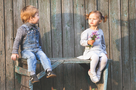 Happy children outdoor at fall season, sitting at bench. First date. Baby boy and girl friendship. Children care. International Children\'s Day.