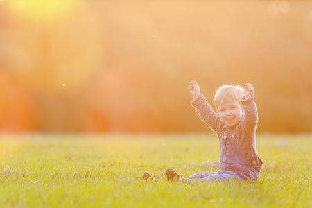 Happy child outdoor at yellow field raised his hands up. Autumn season. Happy Family Values. Baby boy. Children care. International Children\'s Day at 20 November or June 1 Universal Children\'s Day