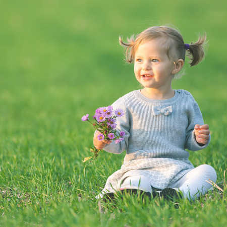 Funny child outdoor at flowers field holding flowers. Autumn season. Happy Family Values. Baby girl. Children care. International Children\'s Day at 20 November or June 1 Universal Children\'s Day