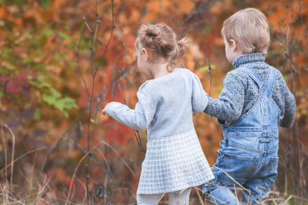 Happy children outdoor at fall season, holding hands. Has a date. Happy Family Values. Baby boy and girl. Children care. International Children\'s Day at 20 November or June 1 Universal Children\'s Day