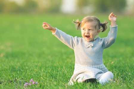 Endless summer. Happy child outdoor at yellow field raised his hands up. Autumn season. Happy Family Values. Girl. International Children\'s Day at 20 November or June 1 Universal Children\'s Day