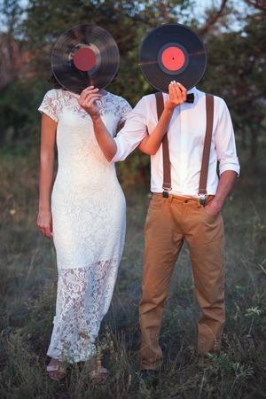 Photo pour Conceptual Image of Man And Woman Hold A Vinyl Record Discs On Their Faces - image libre de droit