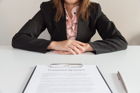 Businesswoman sitting with employment agreement in front of her.