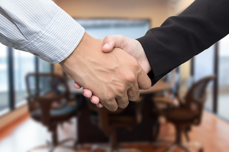 Close up of businessmen shaking hands in meeting room.の写真素材