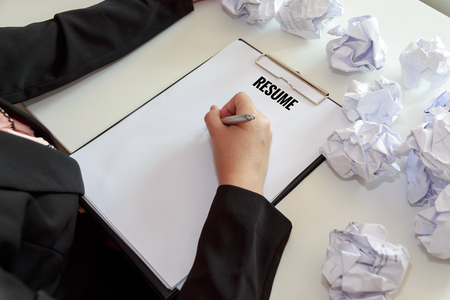Photo pour Hands of female writing resume with crumple sheets of papers at the office desk. - image libre de droit