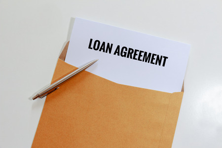 Loan agreement in envelope with pen on table - business concept.
