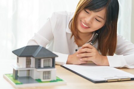 Photo for Smile woman looking at home and getting ready to sign contract for investment - satisfy in home - Royalty Free Image