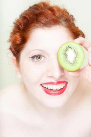 beautiful red hair and lips girl with kiwi on white background