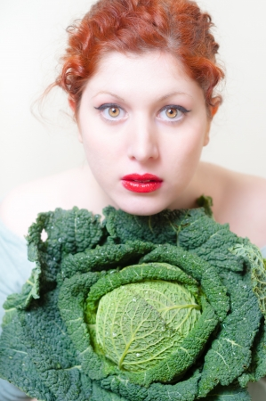 beautiful red hair and lips girl with savoy cabbage on white background