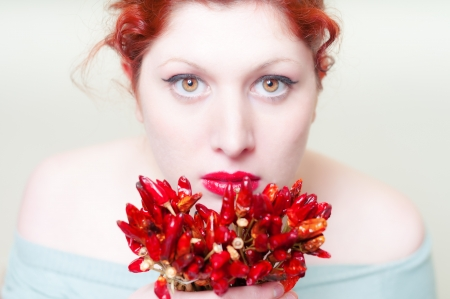 beautiful red hair and lips girl with red chillies on white background