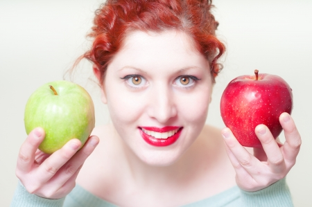 beautiful red hair and lips girl with green and red apple on white background