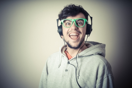 Foto de boy with sweatshirt and headphones on gray background  - Imagen libre de derechos