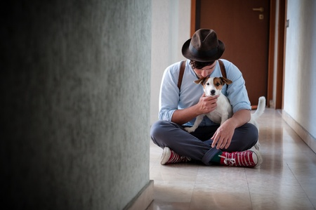hipster young man posing with jack russell dog in a hallway