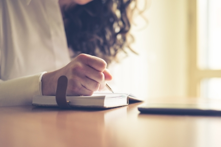 beautiful woman at home writing and working with diary and smart phone