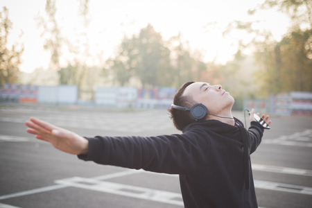 Photo for young crazy funny asian man in town outdoor lifestyle listening music with headphones - Royalty Free Image