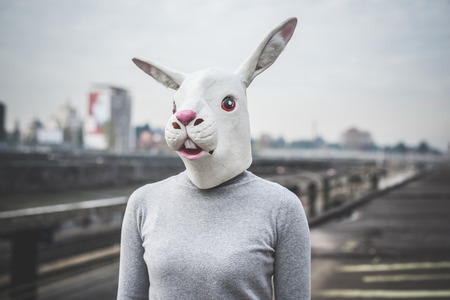 surreal woman with a rabbit mask - conceptual shot in urban landscape