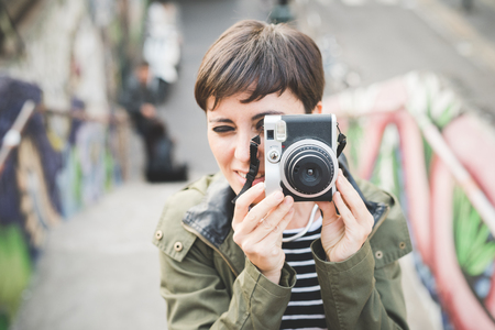 Photo pour Half length of young handsome caucasian brown straight hair woman taking a photo with vintage camera - artist, creative concept - image libre de droit