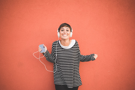 Half length of young handsome caucasian brown straight hair woman listening music with headphones leaning against a wall, looking in camera smiling, holding smartphone - technology, music concept