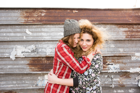 Half length of two young curly and straight blonde hair caucasian woman hugging, smiling and having fun together - carefree, youthful, friendship, concept